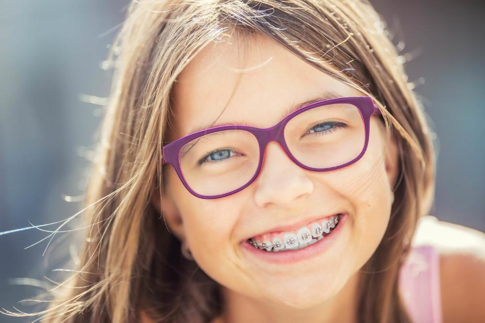 young girl with glasses and braces smiling