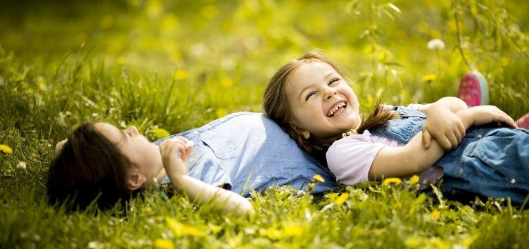 Two young girls laying in the grass