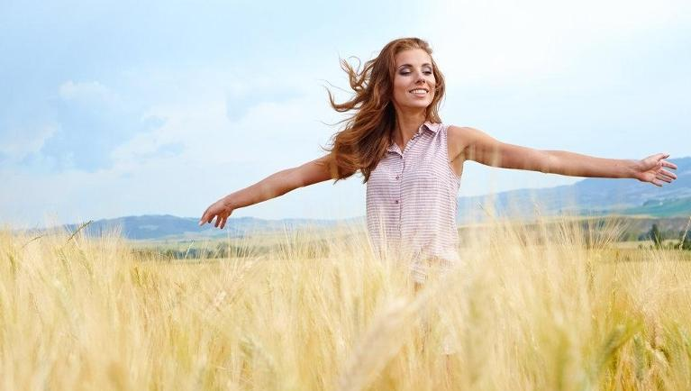 Woman standing in field with arms outstretched